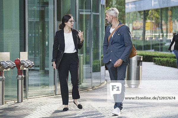 Geschäftsleute beim Spaziergang auf dem Bürgersteig an einer Glaswand in der Stadt