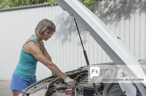Reife Frau repariert Pannenfahrzeug