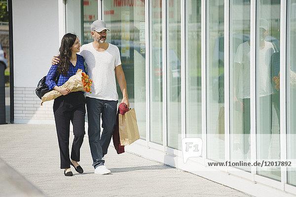 Volle Länge des Paares auf dem Bürgersteig durch die Glaswand in der Stadt an einem sonnigen Tag.