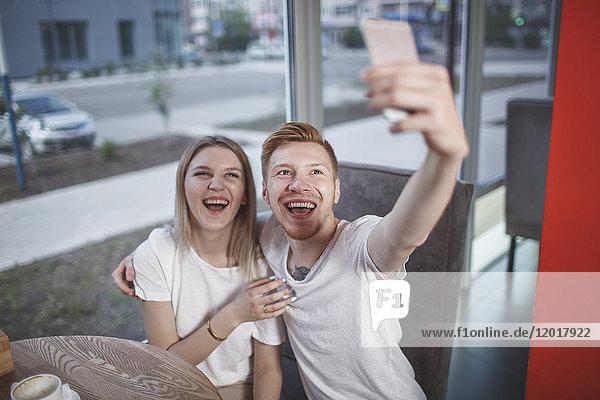Großer Blickwinkel auf ein glückliches junges Paar  das im Restaurant sitzt und sich selbst mit dem Handy fotografiert.