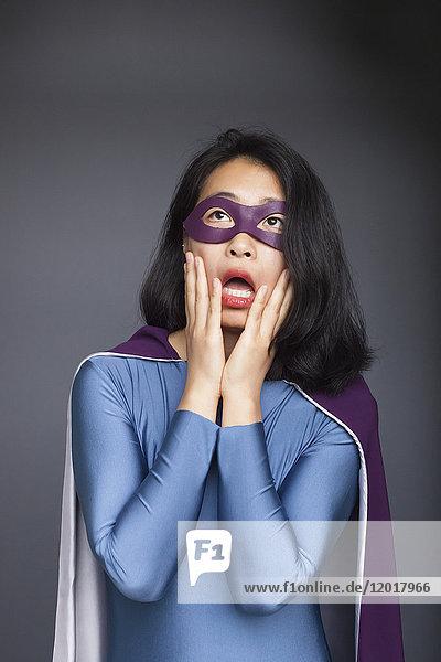 Überraschte Frau in Superheldenkostüm stehend mit Kopf in Händen vor grauem Hintergrund