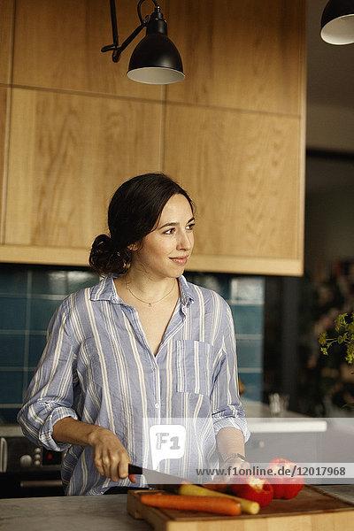 Frau schaut weg  während sie auf der Kücheninsel Karotten hackt.