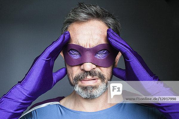 Nahaufnahme eines Superhelden mit Kopfschmerzen vor grauem Hintergrund
