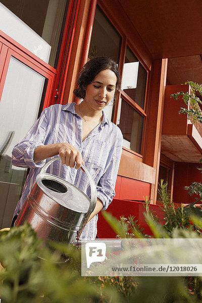 Junge Frau beim Gießen von Pflanzen auf dem Hof