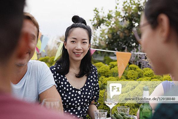 Glückliche junge Frau sitzend mit Freunden auf der Terrasse