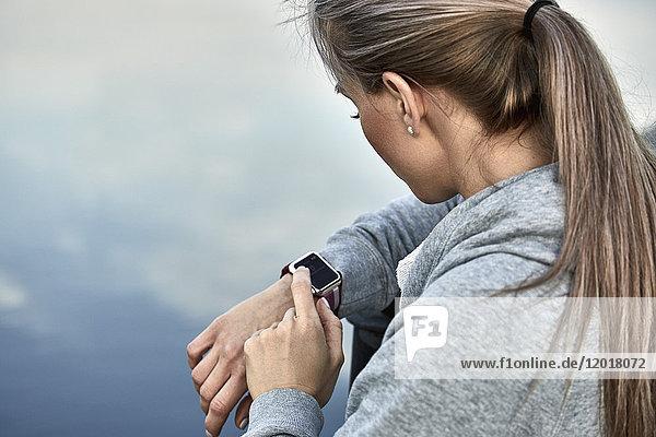 Hochwinkelansicht der Frau mit intelligenter Uhr gegen den See