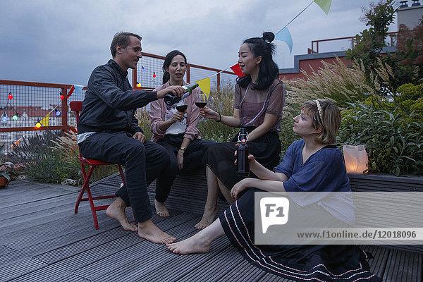 Mann serviert Rotwein an Freundin während der Party auf der Terrasse