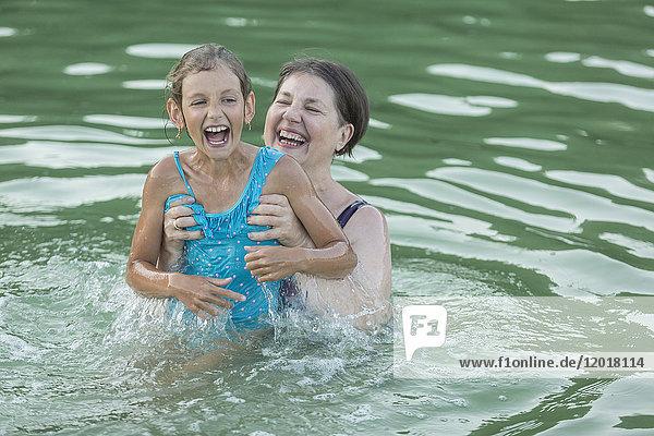 Lächelnde Großmutter genießt mit Enkelin beim Schwimmen im Pool