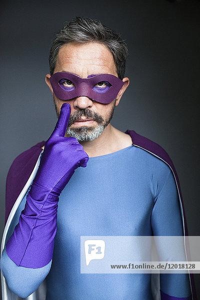 Porträt eines selbstbewussten Superhelden vor grauem Hintergrund