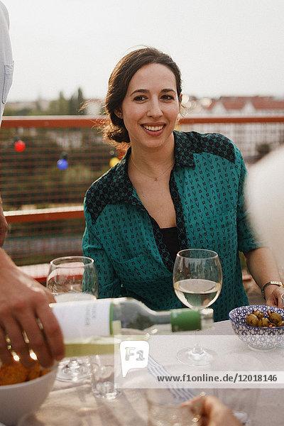 Fröhliche Frau sitzt am Mittagstisch auf der Terrasse
