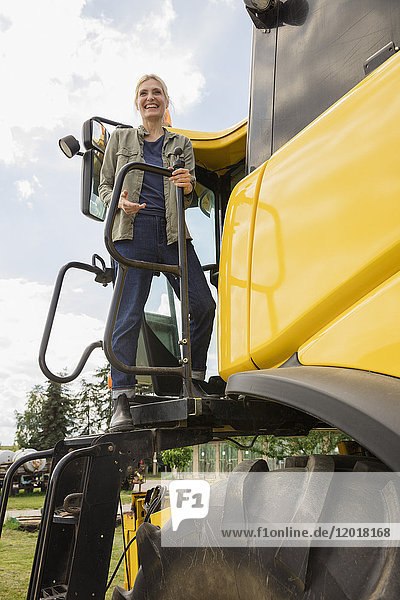 Niedriger Blickwinkel der glücklichen Frau auf dem Traktor gegen den klaren Himmel