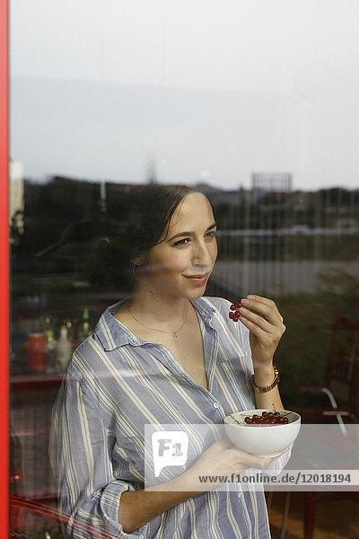 Nachdenkliche junge Frau isst rote Johannisbeeren  während sie durchs Fenster schaut.