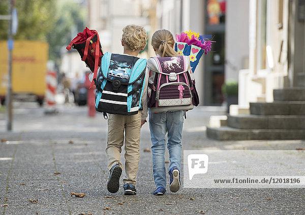 Zwei Kinder mit Schultüte auf Schulweg  von hinten