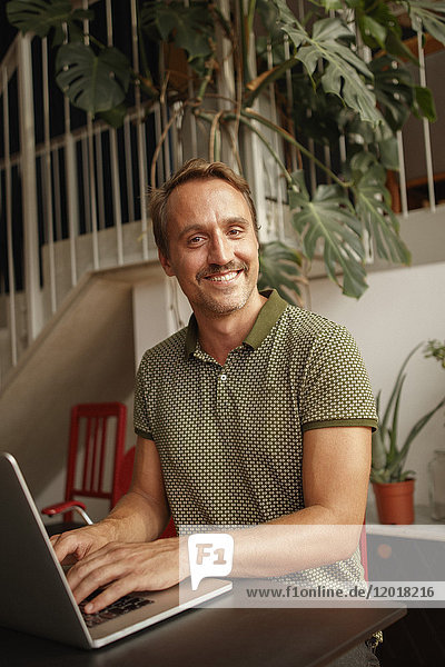 Porträt eines glücklichen mittleren Erwachsenen mit Laptop am Tisch