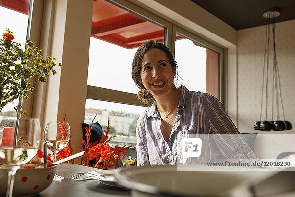 Glückliche junge Frau schaut weg  während sie am Esstisch sitzt.