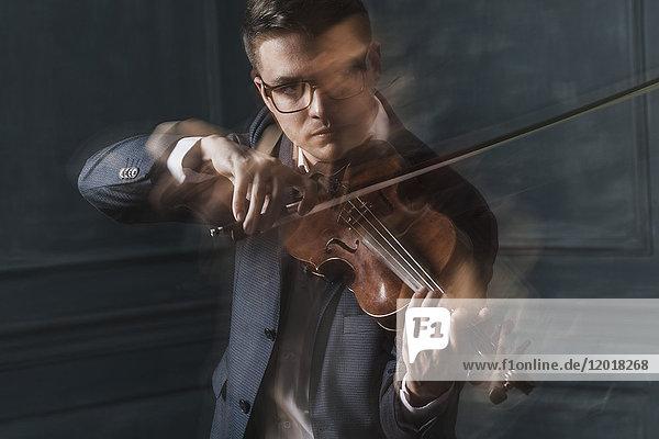 Verschwommene Bewegung eines selbstbewussten Geigers  der Geige gegen Wand spielt.