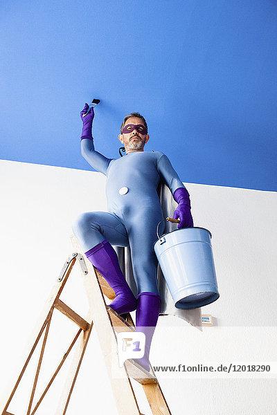 Portrait eines Superhelden  der auf einer Leiter mit Eimer an der Wand steht.