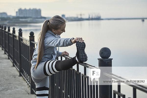 Seitenansicht einer Athletin  die sich auf dem Fußweg auf dem Geländer ausdehnt  Blagoveshchensk  Amur  Russland