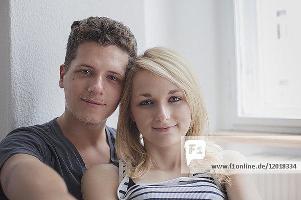 Porträt eines jungen Paares  das zu Hause sitzt