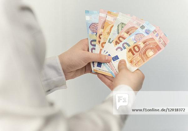 Gefächerte Euroscheine in zwei Händen