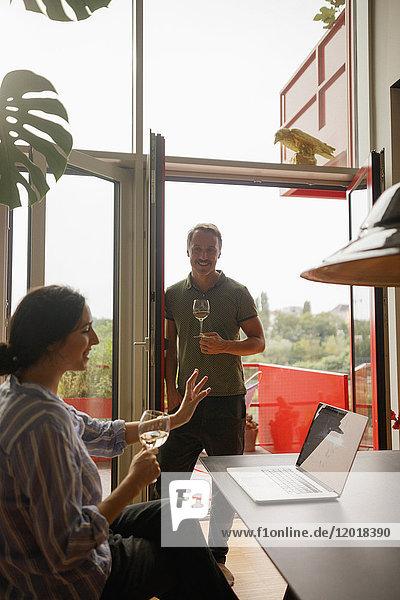 Mann  der die Frau mit dem Laptop betrachtet  während er zu Hause Weinglas hält