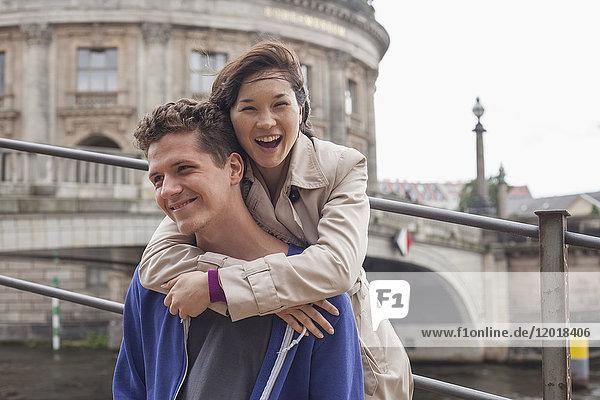 Niederwinkel-Porträt einer fröhlichen Frau  die einen männlichen Freund gegen das Bode-Museum umarmt.
