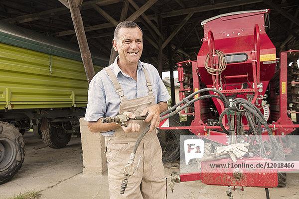 Glücklicher reifer Landwirt bei der Arbeit mit Landmaschinen