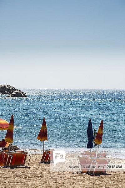 Geschlossene Sonnenschirme mit Liegestühlen am Strand gegen klaren blauen Himmel an sonnigen Tagen