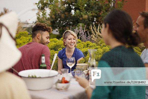 Glückliche männliche und weibliche Freunde sitzen am Außentisch auf der Terrasse.