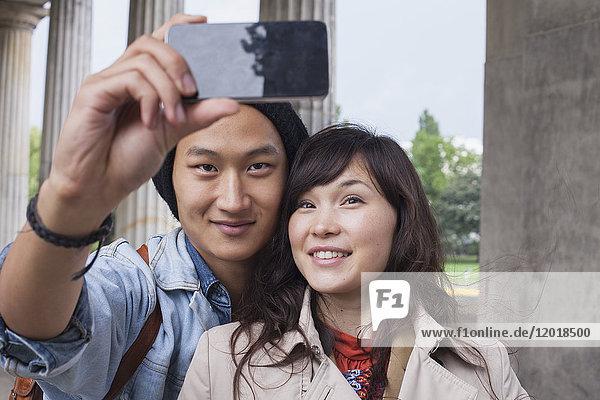 Lächelnder Mann nimmt Selfie mit junger weiblicher Freundin mit