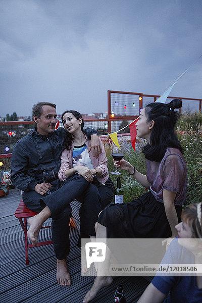 Ein glückliches Paar  das in der Abenddämmerung mit Freunden auf der Terrasse sitzt.
