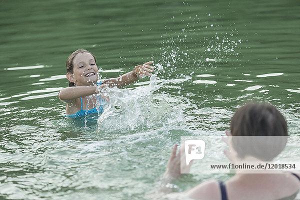 Großmutter und Enkelin planschendes Wasser im Schwimmbad