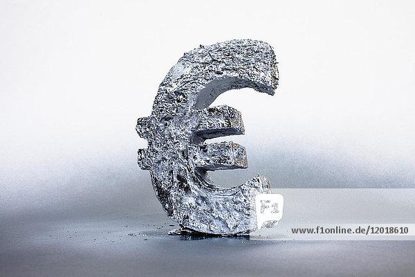 Nahaufnahme des silbernen Euro-Symbols vor grauem Hintergrund