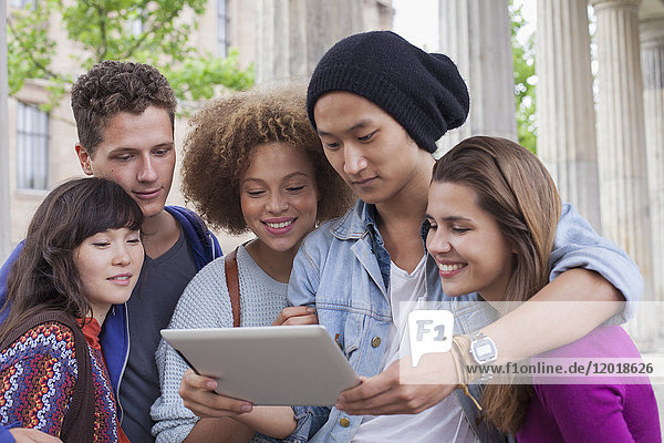 Junger Mann zeigt digitales Tablett für multiethnische Freunde