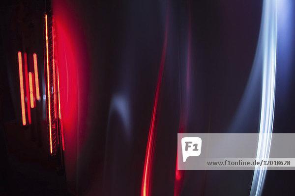 Vollbildabstraktes Bild von roten und grauen Lichtspuren vor schwarzem Hintergrund