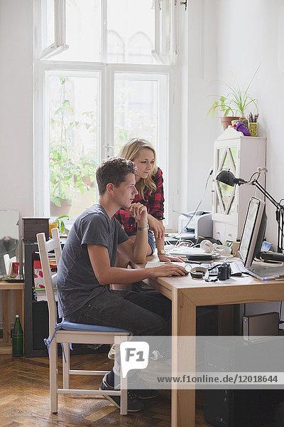 Junges Paar mit Computer am Tisch gegen Fenster