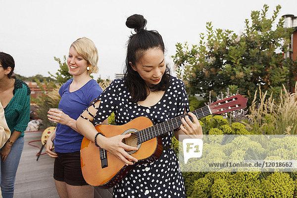 Junge Frau spielt Gitarre auf der Terrasse  während weibliche Freunde im Hintergrund stehen.