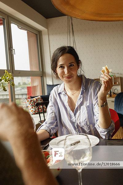 Lächelnde Frau hält Brot  während sie den Mann im Haus ansieht.