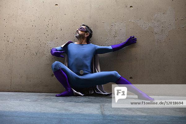 Superheld kauert gegen die Wand
