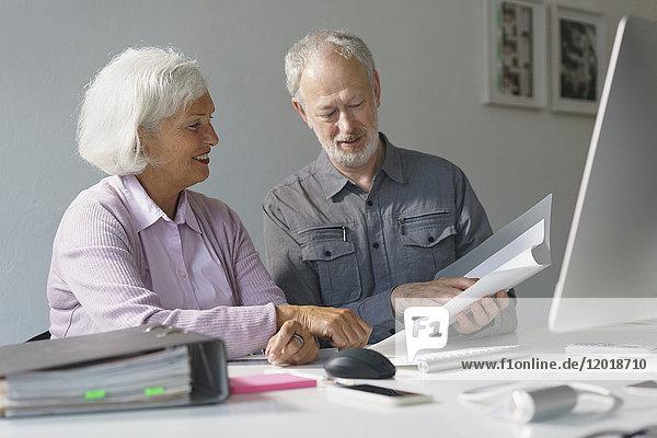 Lächelnde Geschäftskollegen diskutieren über Dokumente am Schreibtisch im Büro