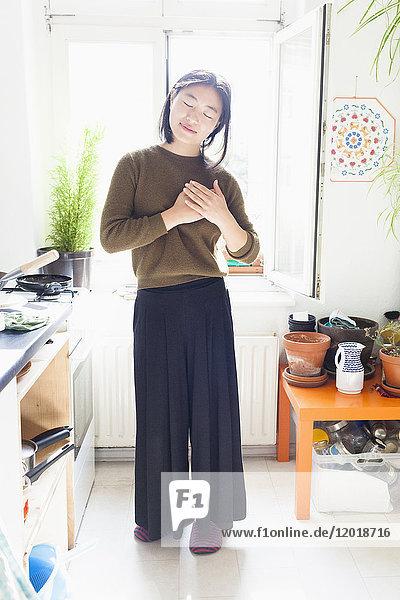 Volle Länge der jungen Frau mit umklammerten Händen am Fenster in der Küche stehend