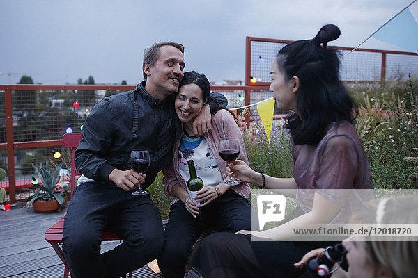 Glücklicher Mann  der die Frau umarmt  während er in der Abenddämmerung mit Freunden auf der Terrasse sitzt.