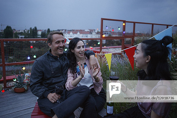 Ein glückliches Paar im Gespräch mit einer Freundin  die Wein auf der Terrasse hält.