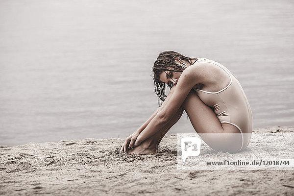 Volle Länge der jungen Frau im einteiligen Badeanzug am Seeufer sitzend