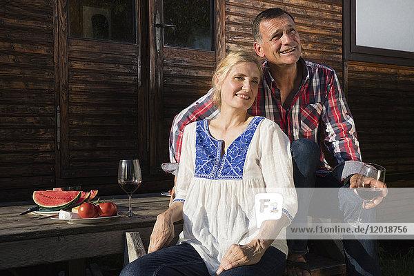 Lächelndes reifes Paar mit Wein und Wassermelone beim Entspannen vor dem Bauernhaus