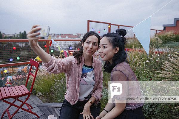 Lächelnde Frauen nehmen Selfie mit Smartphone auf der Terrasse