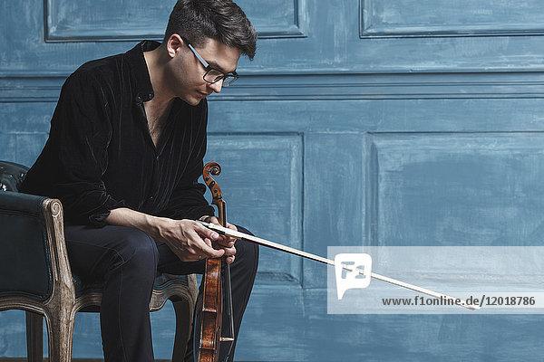 Junger Mann hält Geige  während er auf einem Stuhl an einer blauen Wand sitzt.