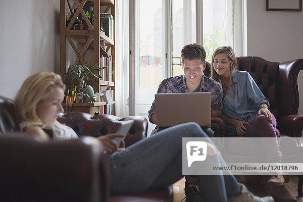 Frau mit digitalem Tablett  während Freunde den Laptop zu Hause benutzen