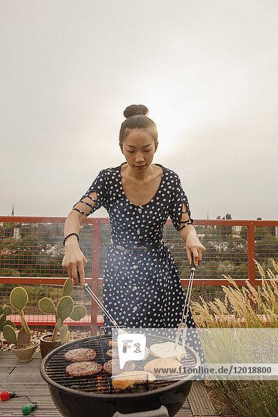 Junge Frau beim Grillen von Steak und Brötchen auf der Terrasse gegen klaren Himmel