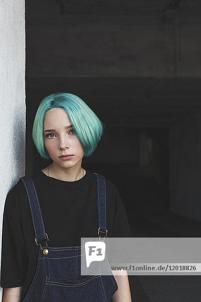 Porträt eines Mädchens  das sich im Keller an die Wand lehnt.